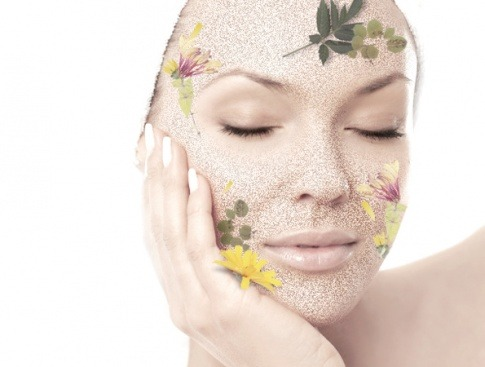 Eine Frau hat als Symbol für eine Kräutertiefenschälkur (Desquamation) Kräuter im Gesicht