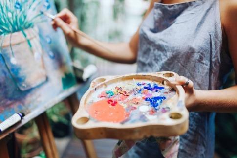 Besondere Geschenkideen neu gedacht: Eine Künstlerin steht vor einer Staffelei und hält eine Farbpalette in den Händen.