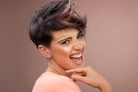 Lächelnde Frau mit Kurzhaarschnitt.