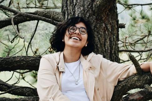 Eine lachende Frau sitzt an einen Baum gelehnt