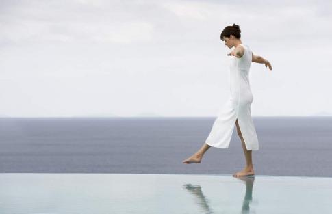 Eine Frau steht auf einem Bein auf einem Abgrund