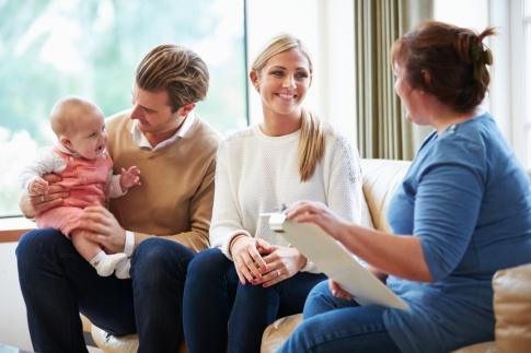 Ein Paar sitzt einer Beraterin gegenüber. Auf dem Schoß des Vaters sitzt ein kleines Kind, welches zufrieden lacht.