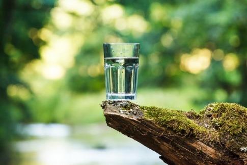 Wasserglas auf einem Stein mit Fluss im Hintergrund.