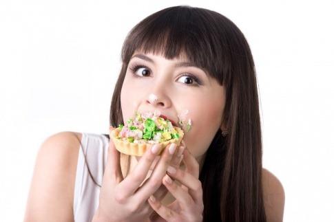 Eine Frau isst Lebensmittel, die Pickel verursachen