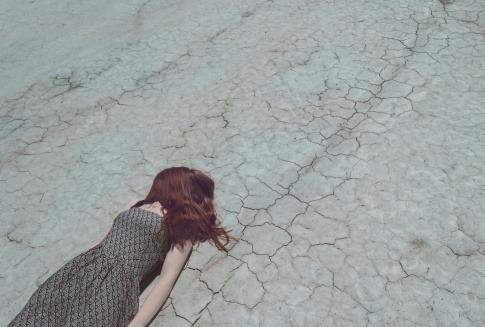 Eine Frau, die ihren Lebenssinn verloren hat, liegt auf einem ausgetrockneten Wüstenweg.