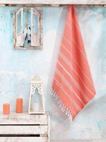 Ein Handtuch in der Farbe Koralle hängt an einer Wand