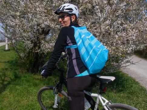 Eine Frau fährt mit einer trendigen Tasche Fahrrad