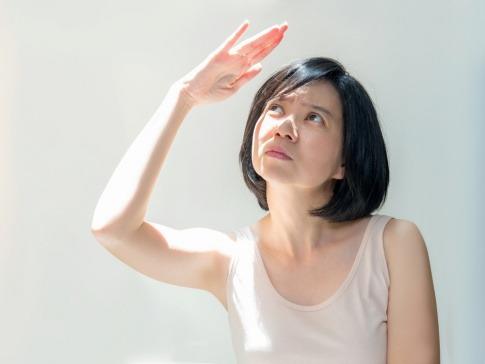 Frau hält die Hand schützend Richtung Sonne