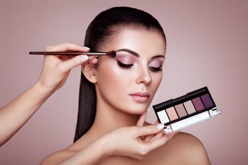 Ein Making off, wo einer Frau mit dunklen langen braunen Haaren ein Augen Make-up geschminkt wird