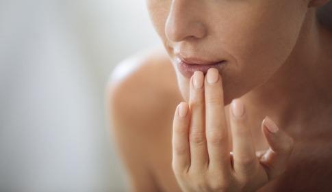 Eine Frau fasst ihre Lippe an