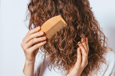 Frau mit lockigen Haaren und Kamm