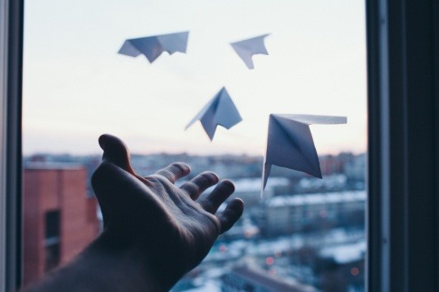 Hand die Papierflieger fliegen lässt