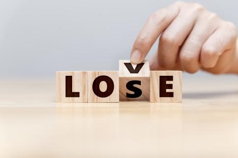 Die Buchstaben auf vier Holzblöcken ergeben das Wort Love. Dreht man jedoch den V-Holzblock, wird aus Love Lose.