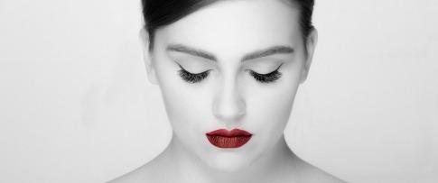 Eine Frau in schwarz-weiß mit roten Lippen hält die Augen zu und trägt Luxuslashes