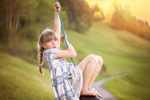 Mädchen macht Bewegung auf einem Seil im Freien.