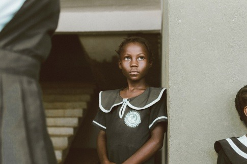 Ein schwarzes Mädchen lehnt an einer Mauer