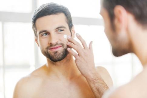 Ein Mann steht vor einem Spiegel für die Männer Gesichtspflege