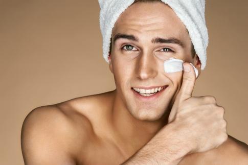 Ein Mann gibt Männerkosmetik ins Gesicht