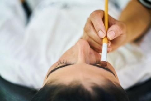 Eine Frau wird mit Make-up geschminkt