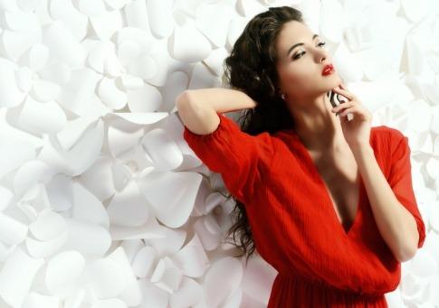 Eine Frau steht vor einer hellen Wand mit rotem Kleid, dunklem Haar und dunklen Augen