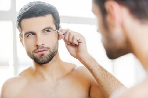 Ein Mann zupft seine Augenbrauen