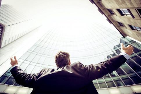 Ein Mann im Anzug steht vor einem modernen Gebäude aus Glas und hebt die Arme in die Luft
