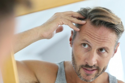 Ein Mann betrachtet seine Haare wegen Ausfall