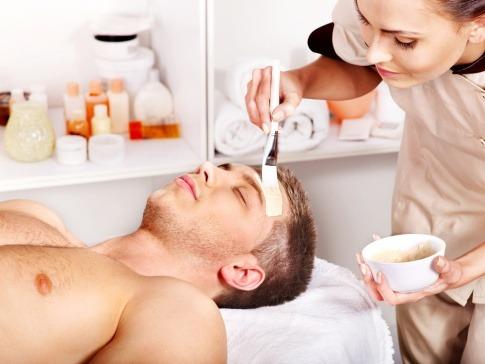Ein Mann liegt in einem Kosmetikstudio bei einer Männer Gesichtspflege