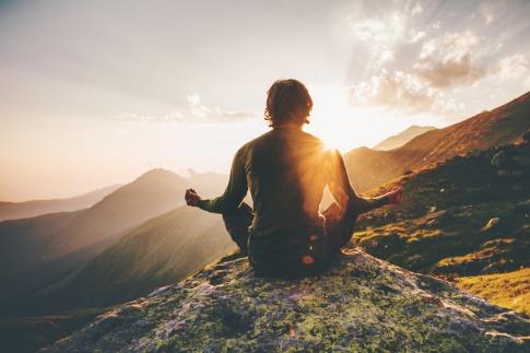 Ein Mann sitzt im Schneidersitz auf einem Berg und meditiert