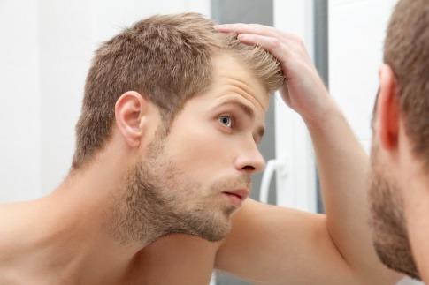 Ein Mann betrachtet seine Falten im Spiegel