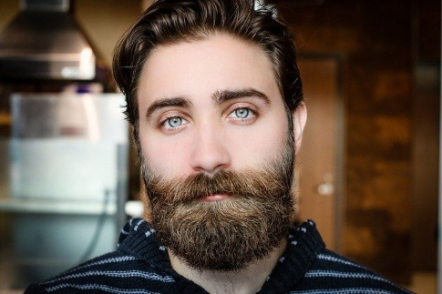 Ein gepflegter Mann mit stechend blauen Augen hat einen Vollbart