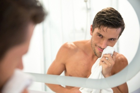 Ein Mann wischt nach der Rasur das Gesicht ab