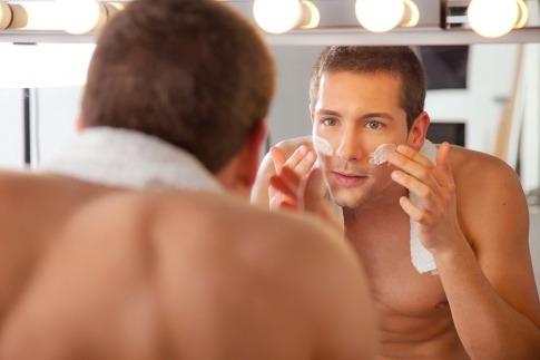 Ein Mann steht bei der Pflege des Gesichts im Bad