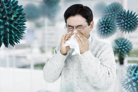 Ein Mann niest und putzt die Nase