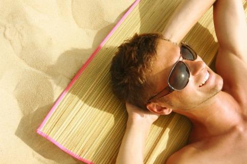 Ein Mann mit einer Sonnenbrille liegt auf einer Matte am Strand und lächelt