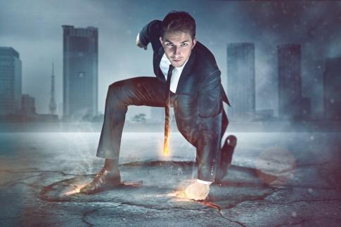 Ein Mann kniet in Superman-Manie am Boden