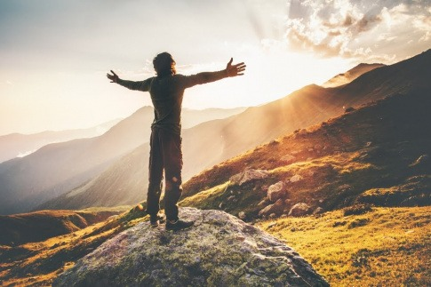 Ein Mann steht mit ausgebreiteten Armen bei Sonnenuntergang auf einem Hügel über dem Meer.