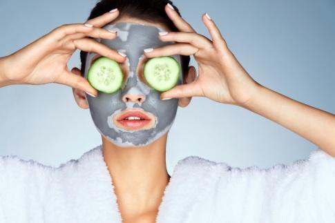 Eine Frau trägt eine Gesichtsmaske und hat zwei Gurkenscheiben auf ihren Augen