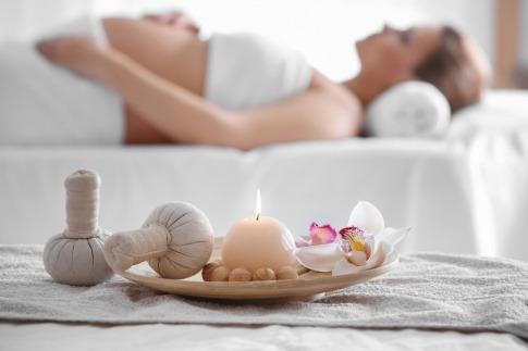 Massageambiente mit schwangerer Frau im Hintergrund