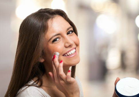 Eine Frau massiert ihre Mimikfalten mit Creme