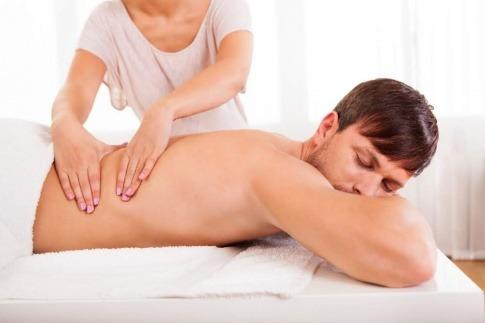 Der Rücken einer Person wird von einer Frau mit lackierten Fingernägeln massiert