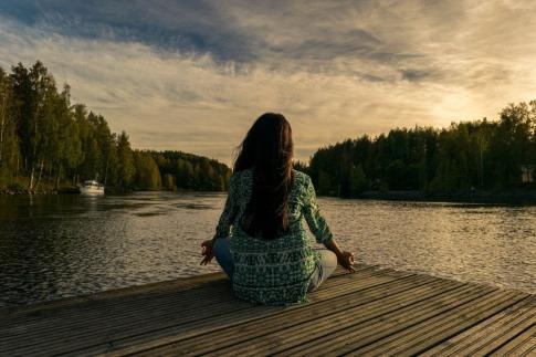 Eine Frau sitzt auf einem Holzsteg am Wasser und meditiert