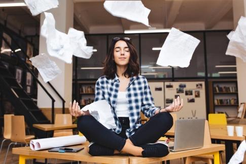 Meditierenden Frau auf einem Büroschreibtisch