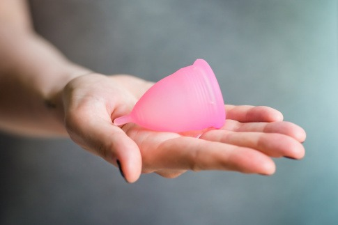 Eine Frau hält eine Menstruationskappe für den Urlaub
