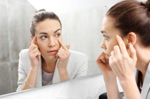 Eine Frau sieht ihre Mimikfalten im Spiegel an