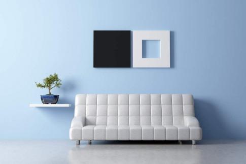 Das Thema minimalistisch Wohnen wird in diesem Bild beispielhaft anhand eines Raums gezeigt, in dem die Einrichtung nur aus einem Sofa, einem Regal mit einer Topfpflanze und einem Bild an der Wand gibt. Der Raum wirkt dennoch einladend und gemütlich.