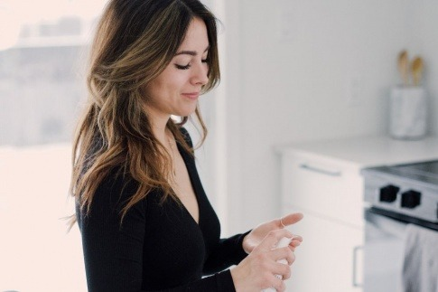 Eine Frau mit Mischhaut cremt ihre Wangen ein