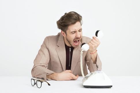 Ein Mann schreit in einen Telefonhörer.