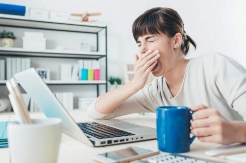 Eine Frau gähnt, während sie am Schreibtisch sitzt. Ihr würden einige Tipps, wie man das Mittagstief umgehen kann, sicherlich helfen.