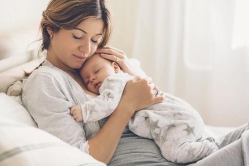 Eine Frau hält ihr Baby und denkt über ein Mommy Makeover nach